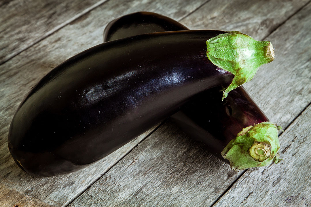 Two raw organic eggplant on old rustic wooden background
